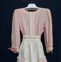 Image of St. Gerald Showtime Costume - This item is a costume used by Mary Lou Harker during a performance of Oklahoma for St. Gerald's Showtime. It is pink in color and features a white apron.