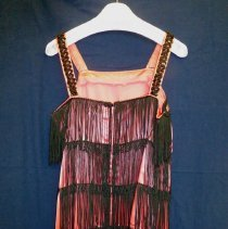 Image of St. Gerald Showtime Costume - This item is a flapper costume used by Mary Lou Harker during a Roaring 20s performance of St. Gerald's Showtime. It is pink in color with black trim.
