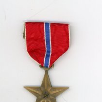 Image of Bronze Star awarded to Joseph F. Lukasek - This item is a Bronze Star medal awarded to former Oak Lawn resident Joseph F. Lukasek for service in World War II. It is contained in a blue case with a white interior. There is also several small pins and bars situated above it. Lukasek served as a staff sergeant in the U.S. Army during World War II.