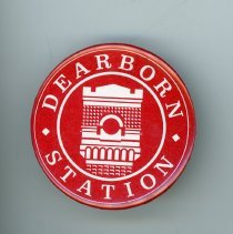 Image of Dearborn Station Button - This item is a Dearborn Station button created by Button Farm located at 8700 South Sproat Avenue in Oak Lawn. It is red in color with white lettering. Formerly a Chicago train station, the Dearborn Station now serves as office and retail space.
