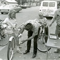Image of VFW Lite-A-Bike Campaign - This is a photograph of the Johnson-Phelps VFW's Lite-A-Bike Campaign. The image shows a veteran helping a girl with her bicycle.