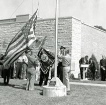 Image of Unveiling the New Village Flag, 1964 - This is a photograph of the unveiling of the new Village Flag in 1964. The image shows the flag being raised in front of the Village Hall. Mayor Fred M. Dumke is standing to the right of the podium.