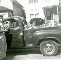 Image of Walt's Tin Shop - This is a photograph of Walter Wettergren and his new truck at an unidentified location. A woman holding an umbrella and several children are in the bed of the truck. Mr. Wettergren operated a heating, air conditioning, and sheet metal business out of his home - Walt's Tin Shop, at 9826 S. 55th Avenue. Homes are seen in the background.