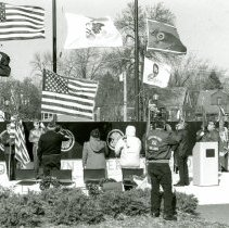 Image of Veteran's Day Service 1998 - This is a photograph of a Veteran's Day memorial service held at the Oak Lawn Veteran's Memorial on the Village Green (Dumke Drive & Cook Avenue) in 1998. Participants are saying the Pledge of Allegiance. The houses in the background are the backs of residential home on the south side of Oak Street between 52nd Avenue and Raymond Drive.
