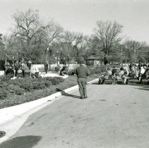 Image of Veteran's Day Ceremony 1998 - This is a photograph of a Veteran's Day ceremony held at the Oak Lawn Veteran's Memorial located at Dumke Drive and Cook Avenue on the Village Green in 1998. In the background, the Village's gazebo and the backs of residential home on the south side of Oak Street between 52nd Avenue and Raymond Drive.