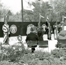 Image of Veteran's Day Ceremony 1998 - This is a photograph of a Veteran's Day memorial service held at the Oak Lawn Veteran's Memorial on the Village Green (Dumke Drive & Cook Avenue) in 1998. Participants are laying a wreath. The houses in the background are the backs of residential home on the south side of Oak Street between 52nd Avenue and Raymond Drive.