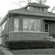 Image of 9338 S. 53rd Court House - This is a photograph of a house, a classic Chicago-style brick bungalow, located at 9338 S. 53rd Court. A Christmas wreath hangs near the front stairs. On the left, garland and a stocking are being strung and a ladder leans against the house nearby.