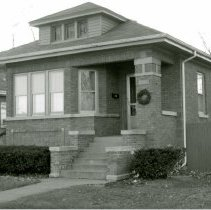 Image of 9338 S. 53rd Court House - This is a photograph of a house, a classic Chicago-style brick bungalow, located at 9338 S. 53rd Court. A Christmas wreath hangs near the front stairs. On the left, garland and a stocking are strung along a fence.