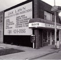 Image of 95th Street Oak Lawn Businesses - This is a photograph of Oak Lawn Photography and Video Productions located at 4949 W. 95th Street. It features the storefront and left (east) side of the building. A pay phone can be seen at the corner of the building. Image 21 Beauty Salon located at 4951, the Village Family Health Clinic located at 4953, and Tuzik's Bakery, located at 4955 W. 95th Street are also visible to the right.