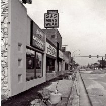 Image of 95th Street Oak Lawn Businesses - This is a photograph of the 5200 block of the south side of 95th Street. Businesses along this block included Angelo's Leathers & Furs at 5209 W. 95th Street, Oak Lawn Office Supply at 5211 W. 95th Street and S & S Men's Wear at 5213 W. 95th Street and the Deja Brew Bar & Grill located at 5219 W. 95th Street. The photo also features road and sidewalk construction on the block. The stoplight at 95th Street and Cook Avenue is visible in the background.