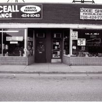 Image of 95th Street Oak Lawn Businesses - This is a photograph of Serviceall Appliance Parts at 4915 W. 95th Street and Dixie Shoe Rebuilders located at 4917 W. 95th Street.  It features the storefront windows with signs advertising services and deals.