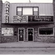 Image of 95th Street Oak Lawn Businesses - This is a photograph of Georges Garages Installations and Repair located at 4923 W. 95th Street and All American Trophy King, Inc. located at 4925 W. 95th Street.  It features the storefronts containing multiple signs advertising their services.