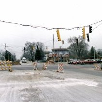 Image of 95th Street and Central Avenue - This is a photograph of repair work at 95th Street and Central Avenue. This view is taken slightly north of 95th Street and looking south. Traffic crossing Central Avenue on 95th is visible. A dentist office on the southeast corner of the intersection is visible in the left of the picture. A billboard and parking lot are visible on the southwest corner of the intersection and Play It Again is partially visible on the northwest corner of the intersection in the very right of the photo.