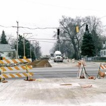 Image of 95th Street and Central Avenue - This is a photograph of repair work at 95th Street and Central Avenue. This view is taken slightly north of 95th Street and looking south. Traffic turning off of Central Avenue is visible and in the background, a road machine can be seen working in the new lanes of Central Avenue. A dentist office on the southeast corner of the intersection is visible in the left of the picture. A billboard and parking lot are visible on the southwest corner of the intersection.