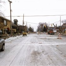 Image of 95th Street and Central Avenue - This is a photograph of repair work at 95th Street and Central Avenue. This view is taken approximately one half block north of 95th Street and looking south. All four corners of the intersection are visible with Play It Again Sports on the northwest corner, Thompson Kuenster Funeral Home on the northeast corner, the Dental Professional building on the southeast corner and the Senese's Comedy Club billboard and parking lot on the southwest corner. In the background, construction workers can be seen working on the street at the intersection and a road machine can be seen in the far background.
