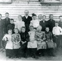 Image of Trinity Lutheran Church German School Students - This is a photograph of Trinity Lutheran Church students posing outside the German School which was located behind the church at 5000 W. 95th Street. Top row, left to right: 1. Fred Holtz, 2. John Hilgendorf, 3. unidentified, 4. Ella Lange, 5. Reverend August Scheffler, 6. unidentified, 7. Al Schultz, 8. John Levine, 9. Elmer Sahs. Front: 1. Agnes Scheffler, 2. Ella Scheffler, 3. Elsie Johrn, 4. Anna Hoffman, 5. Ora Holm, 6. Elizabeth Burger, 7. unidentified.
