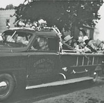 Image of Green Oaks Kiddyland - This is a photograph featuring kids riding in the Green Oaks Kiddyland amusement park fire truck in one of Oak Lawn's Round Up parades. The Green Oak Kiddyland amusement park was formerly located at 95th and Pulaski (Crawford). The park operated from 1946 to 1971.