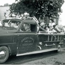 Image of Oak Lawn Round-Up Days - This is a photograph of Oak Lawn Round-Up participants riding in Kiddyland's Green Oaks Fire Department truck. The Green Oak Kiddyland amusement park was formerly located at 95th and Pulaski (Crawford) and operated from 1946 to 1971.