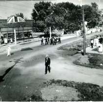 Image of WWI Welcome Home Parade - This is a photograph of a welcome home parade for World War I veterans (which included one woman, Enid Auschwitz). Looking east on 95th Street, the photo shows Behrend's Hardware Store on the northwest corner of Raymond Avenue and 53rd Avenue on the south side. James Montgomery, the first village president, is shown crossing the street in the foreground. Edward A. Biggs, village attorney, gave the welcoming address from the platform on the right.