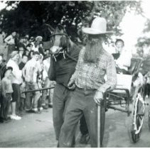 Image of Oak Lawn Round-Up Days - This is a photograph of a 'horse' and buggy in the Oak Lawn Round-Up parade. The 'horse' is a person in a costume being led by another person.