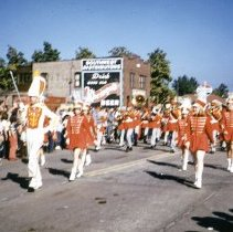 Image of Oak Lawn Round-Up Days Parade - This is a photograph of the Oak Lawn Round-Up Days Parade.  It features a marching band and drum majorettes moving westbound on 95th Street. In the background, Oak Lawn Beer Distributing located at 5510 W. 95th Street, the sign for Spitzer's Standard Gas Station located at 5508 W. 95th Street. and the Oak Lawn water tower, located at 9437 S. Cook, can be seen.