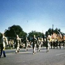 Image of Oak Lawn Round-Up Days Parade - This is a photograph of the Oak Lawn Round-Up Days Parade. It features United States Army Soldiers marching westbound on 95th Street at about 50th Avenue. Oak Lawn Motors and Brakes, located at 5000 W. 95th Street can be seen in the background.