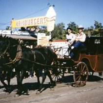 Image of Oak Lawn Round-Up Days Parade - This is a photograph of the Oak Lawn Round-Up Days Parade. It features an old stagecoach moving westbound on 95th Street at about 55th Street as spectators line the sidewalk and watch from the roof tops. In the background is Zale's Frozen Custard located at 5540 W. 95th Street. The brick building partially visible behind the stagecoach is Oak Lawn Beer Distributing located at 5510 W. 95th Street.