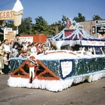 Image of Oak Lawn Round-Up Days Parade - This is a photograph of the Oak Lawn Round-Up Days Parade. It features the Oak Lawn Chamber of Commerce float. Spectators can be seen lining the sidewalks and on the nearby roof tops. In the background is Zale's Frozen Custard located at 5540 W. 95th Street and Oak Lawn Beer Distributing located at 5510 W. 95th Street.
