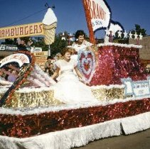 Image of Oak Lawn Round-Up Days Parade - This is a photograph of the Oak Lawn Round-Up Days Parade. It features two women riding the Brandt & Son float. In the background, Zale's Frozen Custard located at 5540 W. 95th Street and Oak Lawn Beer Distributing located at 5510 W. 95th Street are visible.