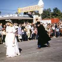 Image of Oak Lawn Round-Up Days Parade - This is a photograph of the Oak Lawn Round-Up Days Parade. It features a suspicious-looking villain in a black cape and hat following a damsel soon to be in distress as spectators watch from the sidewalk and rooftop. In the background is Zale's Frozen Custard located at 5540 W. 95th Street and red trailers marked Southwest Distributing that belong to Oak Lawn Beer Distributing located at 5510 W. 95th Street.