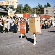 Image of Oak Lawn Round-Up Days Parade - This is a photograph of the Oak Lawn Round-Up Days Parade. It features two participants in box costumes. One is Old Gold Cigarettes and the other is Ohio Matches. They are being followed by a horse drawn vehicle. Spectators lines the sidewalks and watch from roof tops. In the background is Zale's Frozen Custard located at 5540 W. 95th Street and red trailers marked Southwest Distributing that belong to Oak Lawn Beer Distributing located at 5510 W. 95th Street.