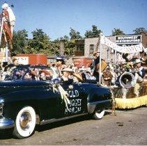 Image of Oak Lawn Round-Up Days Parade - This is a photograph of the Oak Lawn Round-Up Days Parade. It features the Superior Carpets float carrying a band being pulled by a car bearing the name Gold Nugget Ranch. Superior Carpets and Rugs was located at 4803 W. 95th Street. In the background, crowds of spectators can be seen lining the sidewalk and watching from the roof of the Zale's Frozen Custard building located at 5540 W. 95th Street. Red trailers marked Southwest Distributing that belong to Oak Lawn Beer Distributing located at 5510 W. 95th Street are also visible. More parade vehicles can be seen following the float.