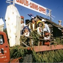 """Image of Oak Lawn Round-Up Days Parade - This is a photograph of the Oak Lawn Round-Up Days Parade. It features participants dressed as cowboys and Indians riding the Oak Lawn Mill and Lumber Company float. The company was located at 9430 S. Cicero Avenue. The sign reads """"cradles, cabins, coffins."""" The float is passing Zale's Frozen Custard located at 5540 W. 95th Street. Spectators can be seen lining the street behind the truck."""