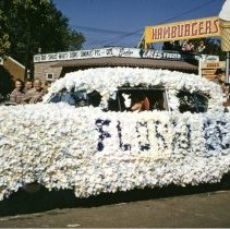 Image of Oak Lawn Round-Up Days Parade - This is a photograph of the Oak Lawn Round-Up Days Parade. It features a car totally covered in flowers. A word is spelled out on the side of the car but is not completely readable. Spectators can be seen lining the sidewalks and watching from the roof top of Zale's Frozen Custard located at 5540 W. 95th Street. Also visible in the background are red trailers with Southwest Distributors signs which belong to Oak Lawn Beer Distributing located at 5510 W. 95th Street.