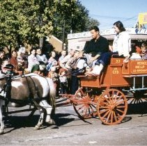 """Image of Oak Lawn Round-Up Days Parade - This is a photograph of the Oak Lawn Round-Up Days Parade. It features a pony drawn wagon. The writing on the wagon says """"Reduce juvenile delinquency, help fire prevention, co-operate with Chicago Fire Department."""" In the background spectators line the sidewalk and watch from the roof top of Zale's Frozen Custard located at 5540 W. 95th Street."""