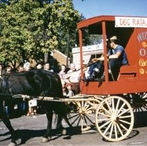 Image of Oak Lawn Round-Up Days Parade - This is a photograph of the Oak Lawn Round-Up Days Parade. It features the Doc Ratajik Wizard Oil wagon. The Ratajik Pharmacy was located at 5269 W. 95th Street. Spectators can be seen lining the sidewalk to watch the parade. In the background is Zale's Frozen Custard located at 5540 W. 95th Street.