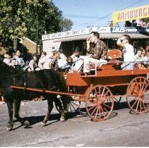Image of Oak Lawn Round-Up Days Parade - This is a photograph of the Oak Lawn Round-Up Days Parade. It features a black pony pulling a little red wagon. In the background, spectators can be seen watching the parade from the sidewalks and from the roof top of Zale's Frozen Custard located at 5540 W. 95th Street.