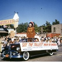 Image of Oak Lawn Round-Up Days Parade - This is a photograph of the Oak Lawn Round-Up Days Parade. It features a car carrying the world's tallest man in America dressed (Donald A. Koehler) as an Indian in the parade as it moves westbound on 95th Street. The sign on the car names two business sponsors, Mode 'O Day and Mal's Men's Shop, both located at 5235 W. 95th Street. Spectators can be seen lining the sidewalks and watching from the roof top of Zale's Frozen Custard located at 5540 W. 95th Street. Also visible in the background are red trailers with Southwest Distributors signs which belong to Oak Lawn Beer Distributing located at 5510 W. 95th Street.