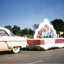 Image of Oak Lawn Round-Up Days Parade - This is a photograph of the Oak Lawn Round-Up Days Parade. It features the Oak Lawn Chamber of Commerce float moving westbound on 95th Street at about 50th Avenue. Oak Lawn Motors and Brakes, located at 5000 W. 95th Street can be seen in the background and spectators can be seen lining the parade route.
