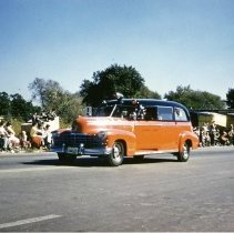 Image of Oak Lawn Round-Up Days Parade - This is a photograph of the Oak Lawn Round-Up Days Parade. It features an orange Columbus Manor Fire District vehicle moving westbound on 95th Street at about 50th Avenue. Oak Lawn Motors and Brakes, located at 5000 W. 95th Street can be seen in the background and spectators can be seen lining the parade route.