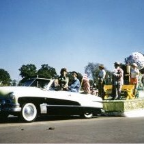 Image of Oak Lawn Round-Up Days Parade - This is a photograph of the Oak Lawn Round-Up Days Parade. It features an unidentified float sporting a golf theme moving westbound on 95th Street at about 50th Avenue. Oak Lawn Motors and Brakes, located at 5000 W. 95th Street, is partially visible in the background and spectators can be seen lining the parade route.