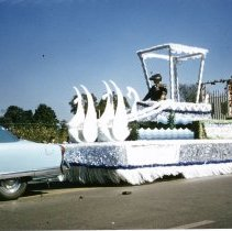 """Image of Oak Lawn Round-Up Days Parade - This is a photograph of the Oak Lawn Round-Up Days Parade. It features a float sponsored by the Regular Democratic Party and Albert H. Brandt, Committeeman. The float appears to have a chariot pulled by white swans and complete with an unidentified driver. Another side on the side of the float lists the """"Blue Ticket"""" candidates for the party. Oak Lawn Motors and Brakes, located at 5000 W. 95th Street, is partially visible in the background and spectators can be seen lining the parade route."""