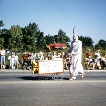 """Image of Oak Lawn Round-Up Days Parade - This is a photograph of the Oak Lawn Round-Up Days Parade. It features a clown pushing a cart westbound on 95th Street just past 50th Avenue. The cart carries an advertising sign that reads 'Don't clown around"""" and has something to do with TV service."""