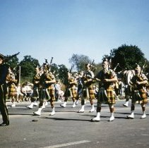 Image of Oak Lawn Round-Up Days Parade - This is a photograph of the Oak Lawn Round-Up Days Parade. It features a group of bagpipers wearing kilts and believed to be part of the American Legion organization. The parade is moving westbound on 95th Street at about 50th Avenue. Oak Lawn Motors and Brakes, located at 5000 W. 95th Street is partially visible in the background and spectators can be seen lining the parade route.
