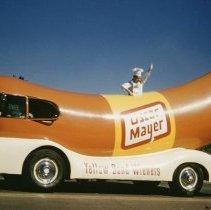 "Image of Oak Lawn Round-Up Days Parade - This is a photograph of the Oak Lawn Round-Up Days Parade.  It features the Oscar Mayer ""Wienermobile."" The parade is moving westbound on 95th Street at about 50th Avenue and spectators can be seen lining the parade route."