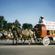 Image of Oak Lawn Round-Up Days Parade - This is a photograph of the Oak Lawn Round-Up Days Parade. It features the horse-drawn liquor wagon with names of local liquor establishments advertised. The parade is moving westbound on 95th Street at about 50th Avenue and spectators can be seen lining the parade route.
