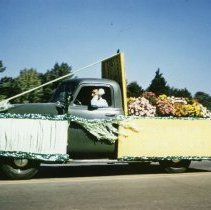 Image of Oak Lawn Round-Up Days Parade - This is a photograph of the Oak Lawn Round-Up Days Parade. It features the Green Thumb Garden Center float. The parade is moving westbound on 95th Street at about 50th Avenue and spectators can be seen lining the parade route.