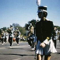 Image of Oak Lawn Round-Up Days Parade - This is a photograph of the Oak Lawn Round-Up Days Parade.  It features a marching band moving westbound on 95th Street just past 50th Avenue. Oak Lawn Motors and Brakes, located at 5000 W. 95th Street, is partially visible in the background and spectators can be seen lining the parade route.