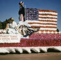 Image of Oak Lawn Round-Up Days Parade - This is a photograph of the Oak Lawn Round-Up Days Parade. It features the Southwest Towns Refuse Disposal Service float decorated with an American flag. A person dressed as Uncle Sam and two women are riding on the float as it moves westbound on 95th Street just past 50th Avenue. Southwest Towns Refuse Disposal Service was located at 4630 W. 95th Street.