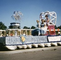 Image of Oak Lawn Round-Up Days Parade - This is a photograph of the Oak Lawn Round-Up Days Parade. It features the Oak Lawn Trust and Savings Bank float moving westbound on 95th Street just past 50th Avenue. Spectators can be seen lining the parade route in the background. Oak Lawn Trust and Savings Bank was located at 5310 W. 95th Street.